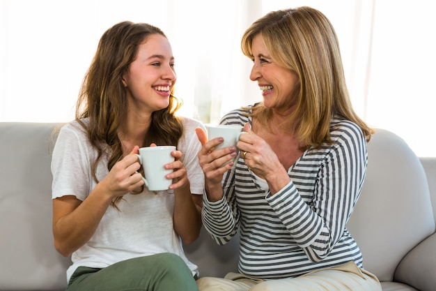 Mãe e filha bebem chá em casa