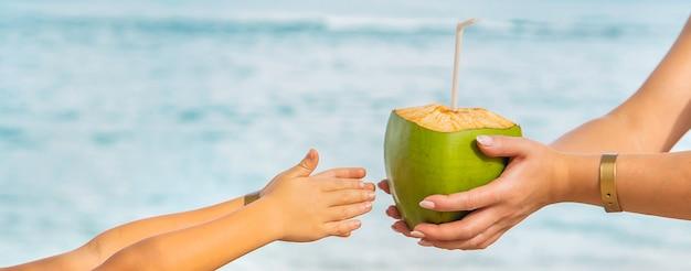 Mãe e filha bebem coco na praia