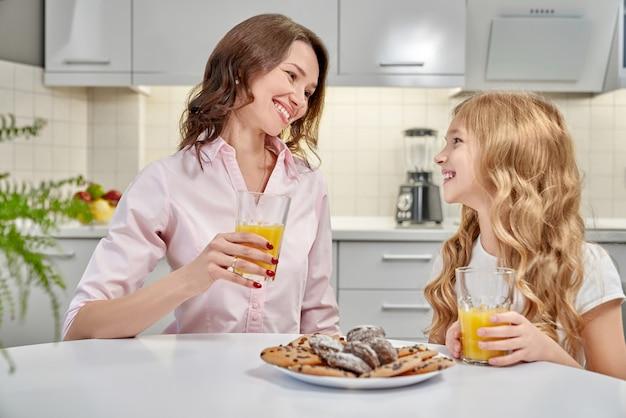 Mãe e filha bebem suco de laranja e comer biscoitos.