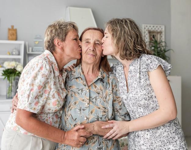 Mãe e filha beijando sua avó em casa