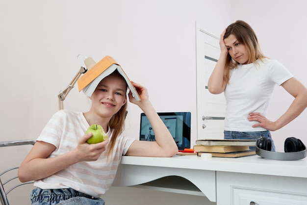 Mãe e filha brigando por lição de casa, mãe chateada está com raiva da filha entediada, educação em casa, mal-entendido
