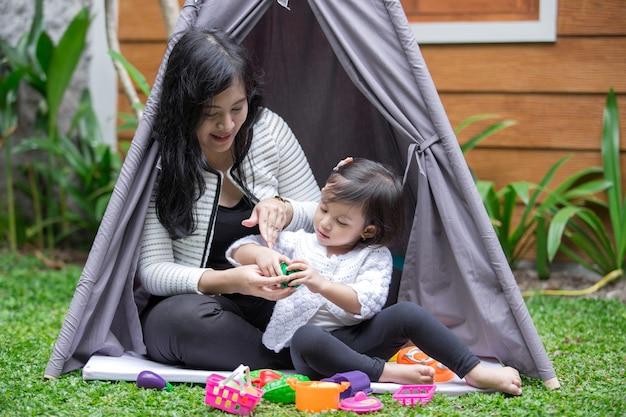 Mãe e filha brincam brinquedos no quintal