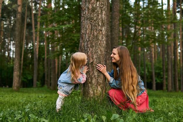 Mãe e filha brincam de esconde-esconde e se divertem no parque