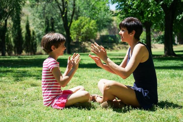 Mãe e filha brincando com as mãos no parque da cidade