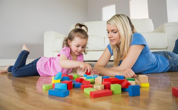 Mãe e filha brincando com blocos de construção no chão