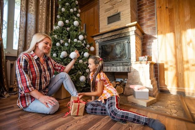 Mãe e filha brincando com bolas perto da árvore de natal. presentes, luzes, bolas de fundo.