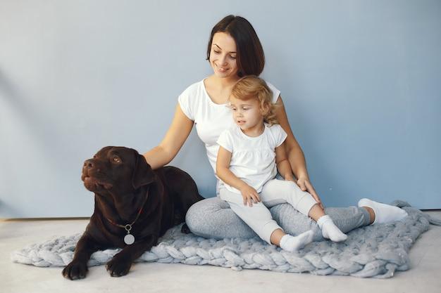 Mãe e filha brincando com cachorro em casa