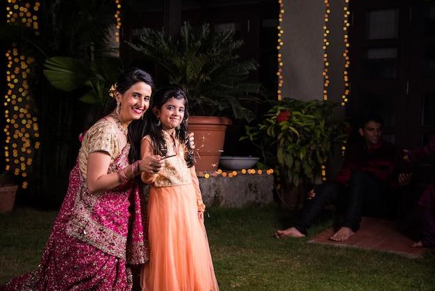 Mãe e filha brincando com fogos de artifício, biscoitos de fogo ou fulzadi na noite de diwali