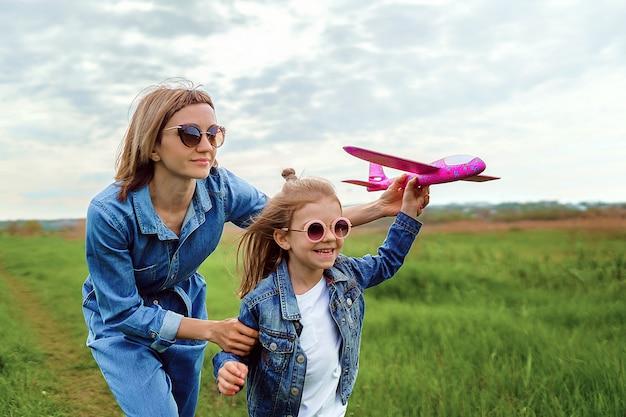 Mãe e filha brincando com o avião de brinquedo