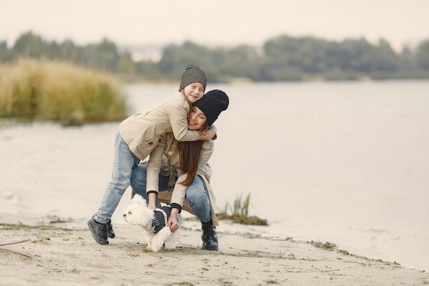Mãe e filha brincando com o cachorro. animal de estimação, animal doméstico e conceito de estilo de vida