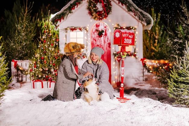 Mãe e filha brincando com o cachorro corgi na neve
