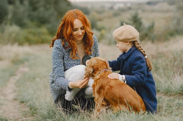 Mãe e filha brincando com o cachorro. família no parque outono. animal de estimação, animal doméstico e conceito de estilo de vida. tempo de outono.