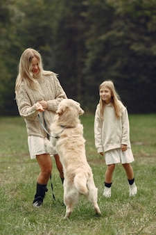 Mãe e filha brincando com o cachorro. família no parque outono. animal de estimação, animal doméstico e conceito de estilo de vida