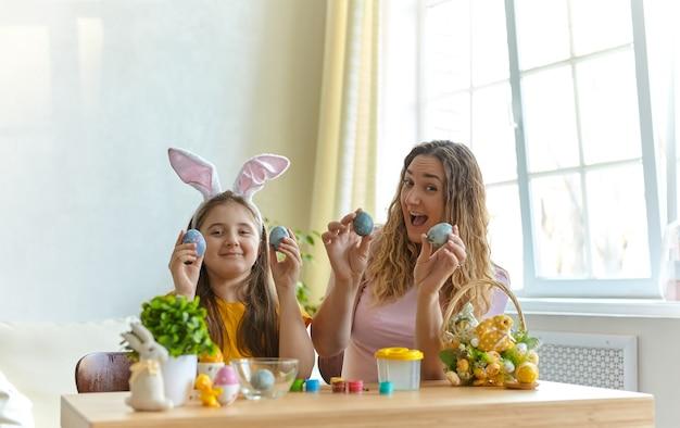 Mãe e filha brincando com ovos pintados. família feliz se preparando para a páscoa. criança menina bonitinha usando orelhas de coelho.