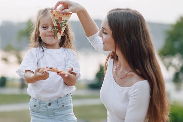 Mãe e filha brincando com pizza na natureza