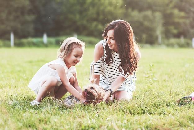 Mãe e filha brincando com um cachorro fofo lá fora, na grama verde