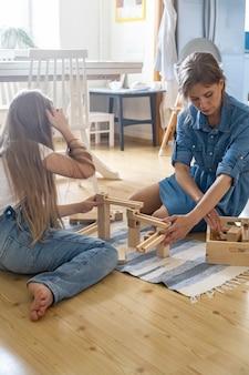 Mãe e filha brincando de brinquedo de bloco de construção de bola de trilha de madeira materiais maria montessori