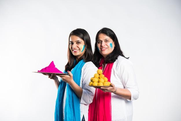 Mãe e filha brincando de holi, segurando um prato cheio de doces laddu e cores. isolado sobre fundo branco