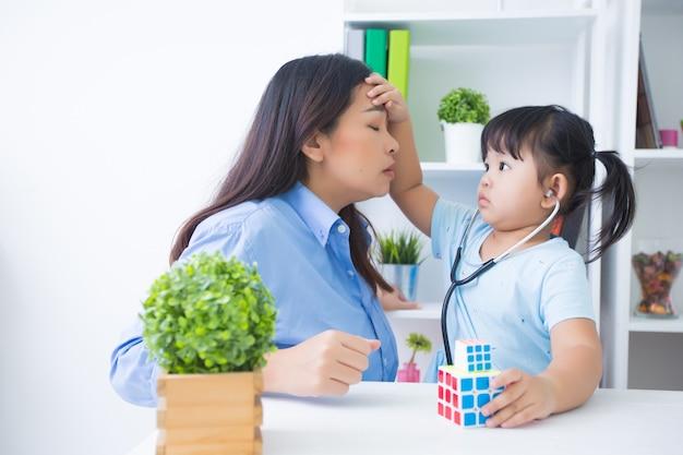 Mãe e filha brincando de médico com estetoscópio