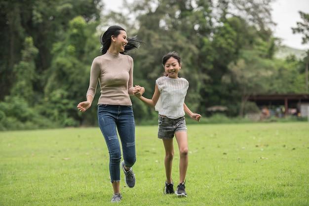Mãe e filha brincando e correndo ao redor do parque