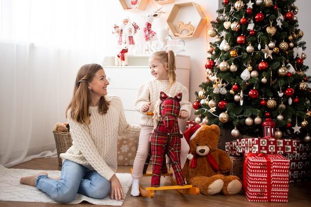 Mãe e filha brincando em casa perto de árvore de natal e caixas de presente