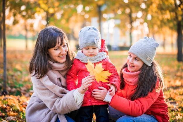 Mãe e filha brincando juntas em passeio de outono no parque
