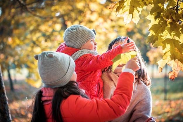 Mãe e filha brincando juntas na caminhada de outono