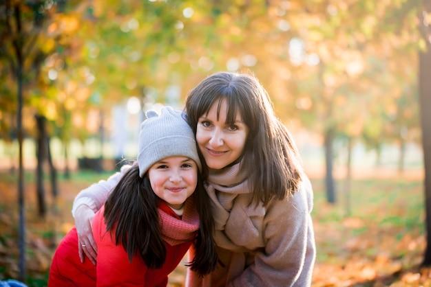 Mãe e filha brincando juntos na caminhada de outono na natureza ao ar livre. jogos ativos de família feliz, estilo de vida no parque amarelo de outono.