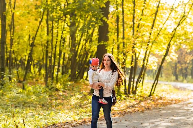 Mãe e filha brincando juntos no parque outono.