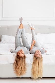 Mãe e filha brincando na cama