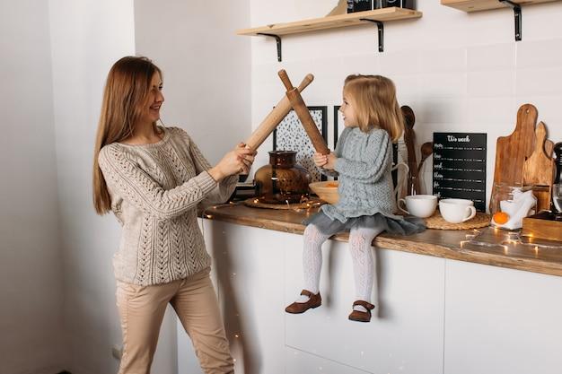 Mãe e filha brincando na cozinha em casa.