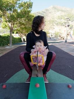 Mãe e filha brincando na gangorra do parque.