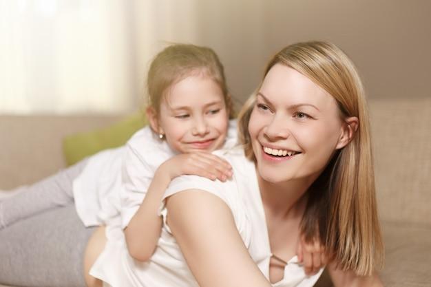 Mãe e filha brincando, sorrindo e se abraçando