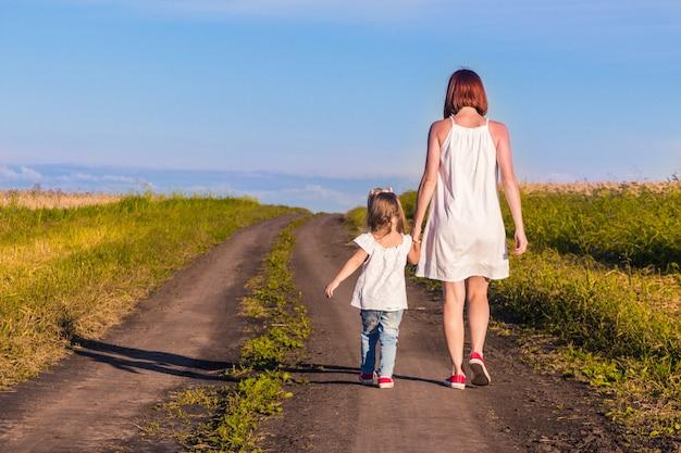 Mãe e filha caminham por uma estrada rural ao longo de um campo de trigo em um dia quente de verão