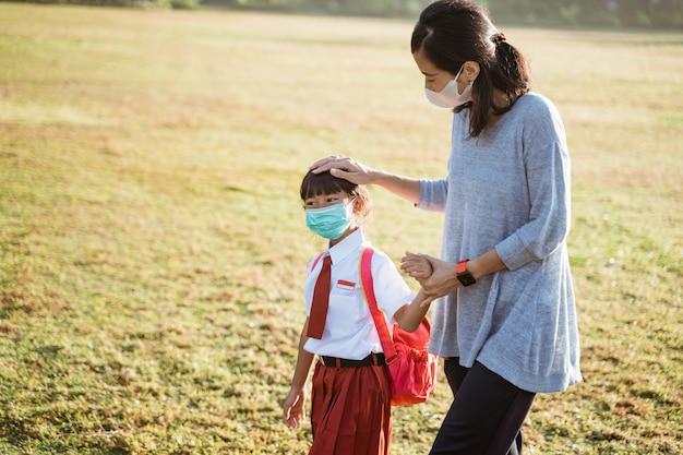 Mãe e filha caminhando juntas e usam máscara facial
