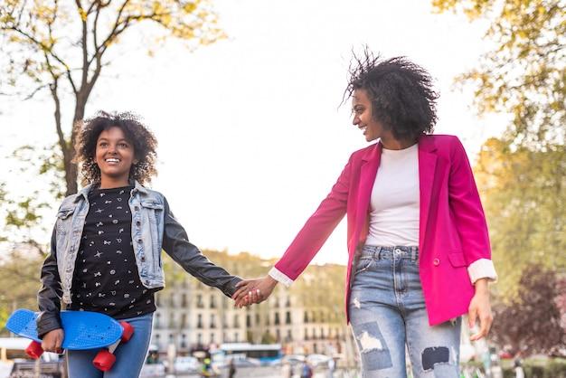 Mãe e filha caminhando juntos ao ar livre