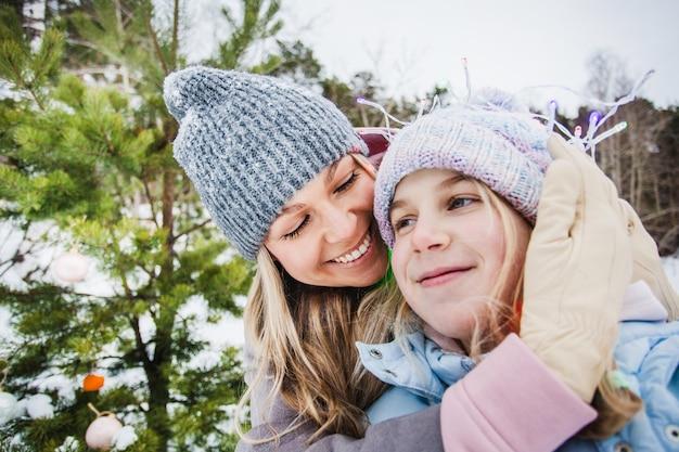 Mãe e filha caminhando na floresta de inverno, árvore de inverno, guirlanda, férias na floresta