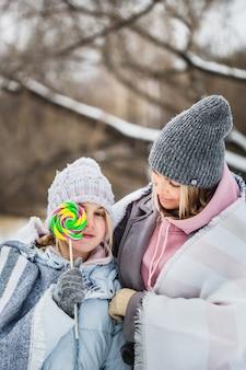 Mãe e filha caminhando na floresta de inverno, envolto em um cobertor, pirulito, pirulito no palito