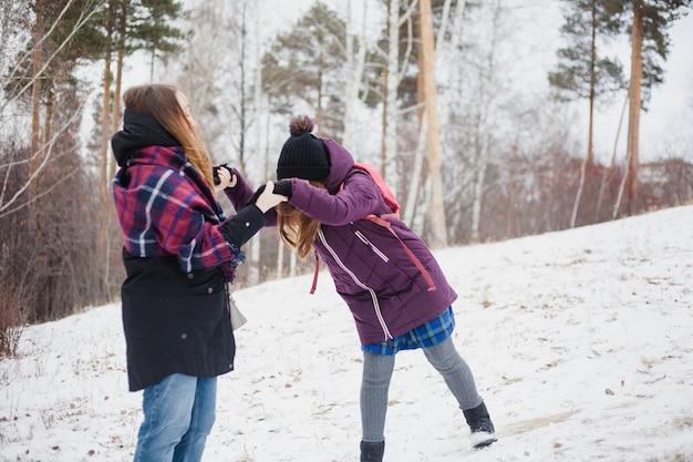 Mãe e filha caminhando na floresta de inverno, parque, caminhadas e caminhadas, roupas de inverno, adolescente