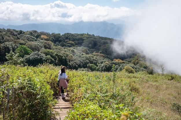 Mãe e filha caminhando nas montanhas em um dia nebuloso na trilha natural de kew mae pan é um paraíso na terra no parque nacional doi inthanon, na tailândia.