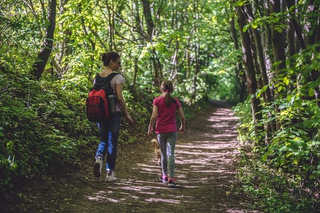Mãe e filha caminhando no caminho na floresta