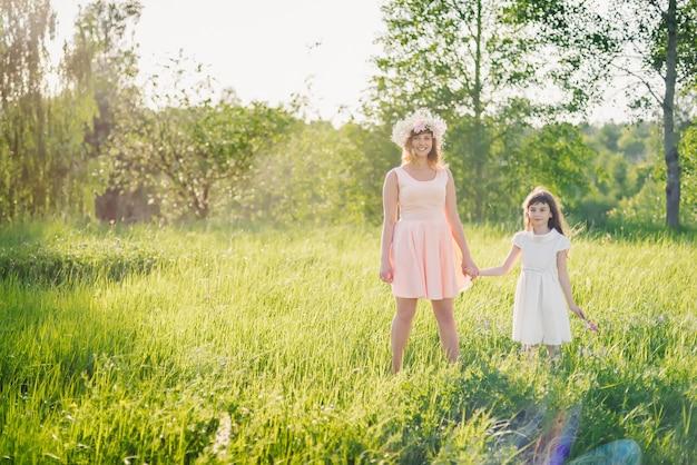 Mãe e filha caminhando no campo no verão dia ensolarado ao pôr do sol