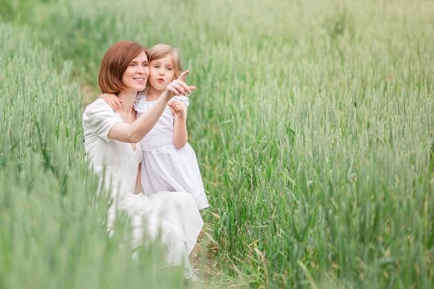 Mãe e filha caminhando no campo