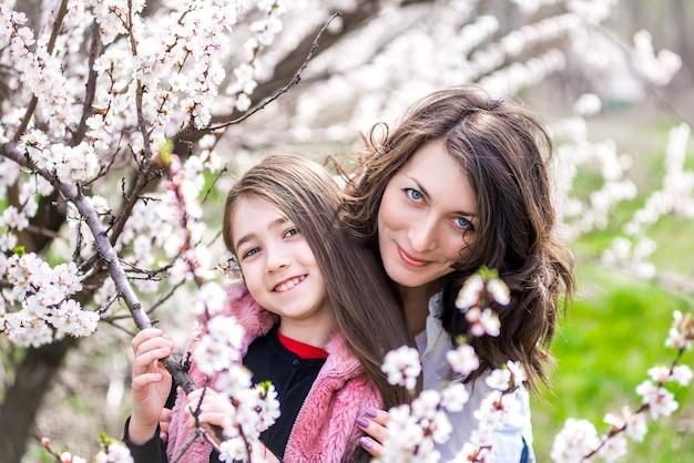 Mãe e filha caminhando no jardim na primavera