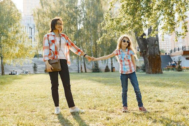 Mãe e filha caminhando no parque de mãos dadas
