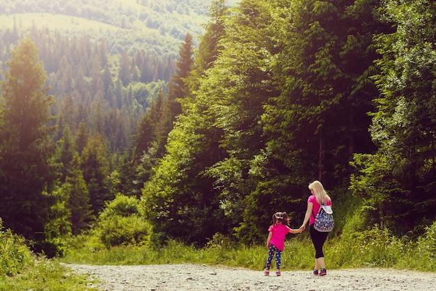 Mãe e filha caminhando pela estrada da montanha