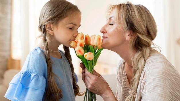 Mãe e filha cheirando buquê de tulipas