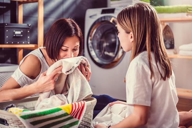 Mãe e filha cheirando toalhas limpas