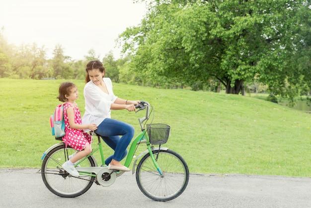 Mãe e filha ciclismo bicicleta juntos.