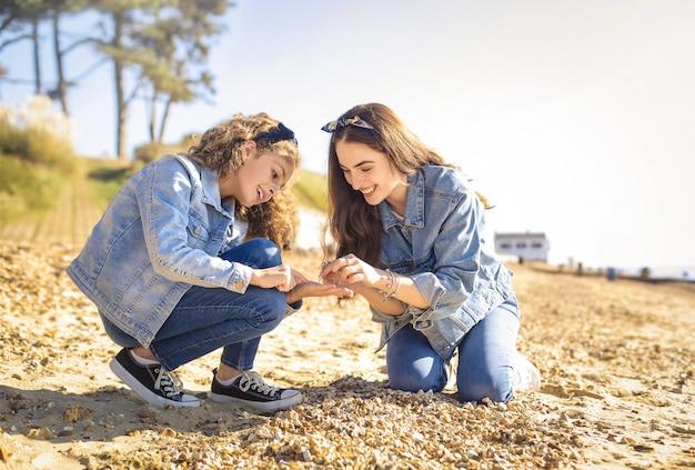 Mãe e filha coletando concha na praia